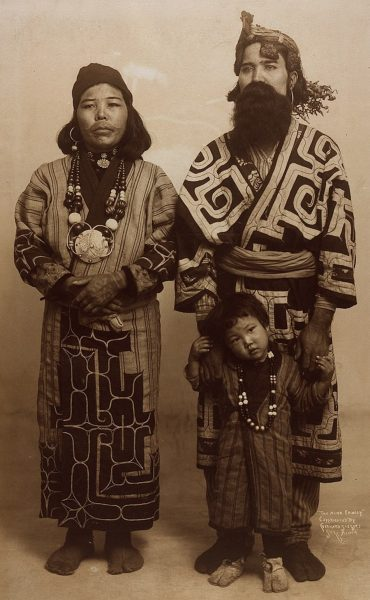 An Ainu family wearing the traditional dress at a world fair in 1904. The Mother has a decorative necklace with a patterned dress with long sleeves and her lips and around her lips are tattooed in a plain colour. The child wears a jumpsuit with a stripe pattern and a beaded necklace. The father wears a dress with a pattern on it like a long coat and long pants. He has a material belt on and the father hold the toddlers hands.