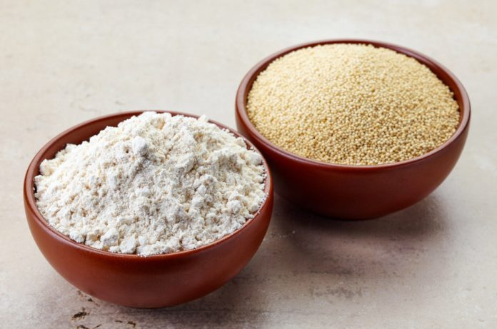 A bowl containing amaranth seeds sits next to a bowl containing amaranth flour.