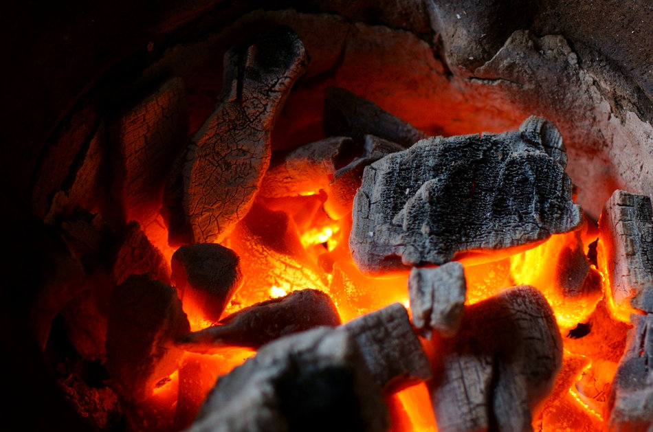 Closeup of charcoal burning in a terracotta kiln.