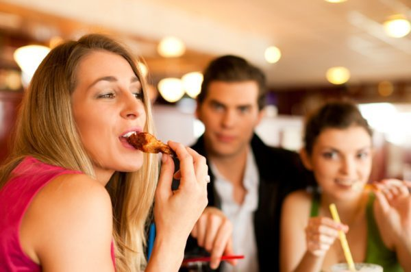 Young blonde woman in red dress takes a bite of a chicken wing while sitting with a couple of friends in a restaurant.