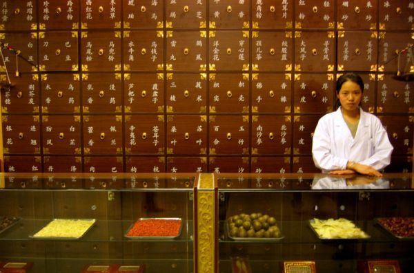 Asian woman in a white lab coat stands behind the counter of a shop selling Chinese medicine.