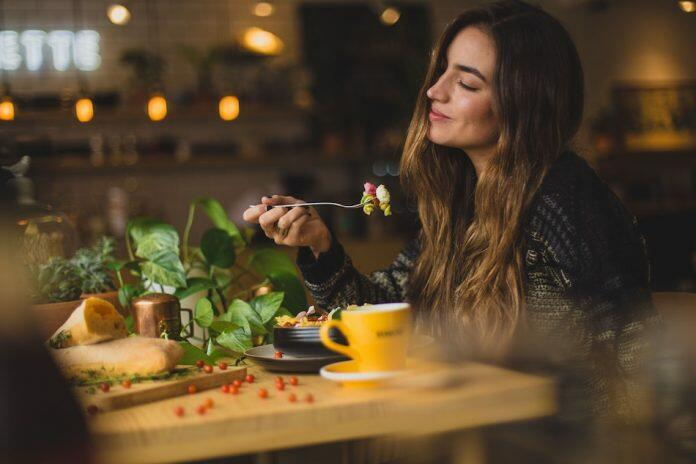 lady eating a meal at a table - eating habits to shift ongoing stress