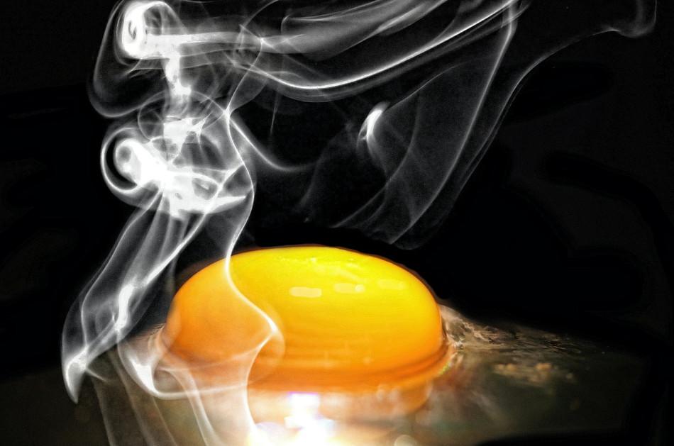 Closeup of an egg yolk frying in a pan.