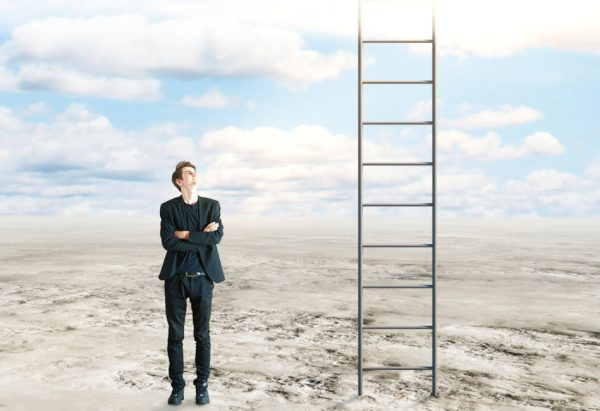 Success and growth concept: Young businessman with folded arms standing in desert and looking up at ladder leading to the sky.