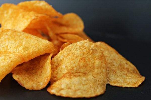 A handful of potato chips sit on a dark countertop.