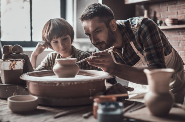 Little boy looking at confident young man drawing on ceramic pot at a pottery class.