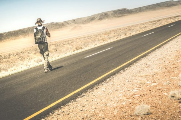 Man with a backpack walking on the road through the Namib Desert in Africa.