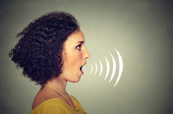 Side profile young woman talking with sound waves coming out of her mouth isolated on grey wall background.