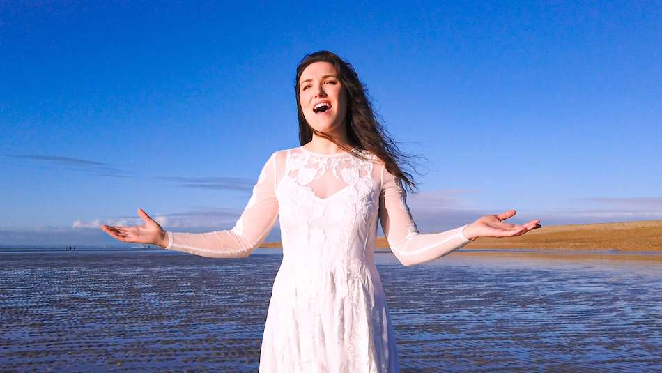 vic may on hastings beach in white dress blue skies she is singing