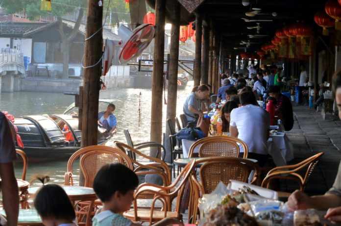 Sidewalk cafe full of customers along a waterway with a man poling a boat in Anchang, China.