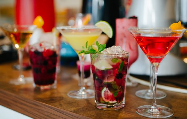 Various colorful cocktails sitting on a counter.