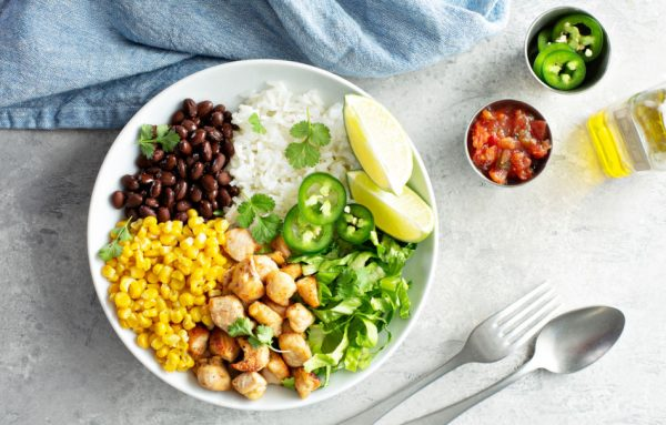 Chipotle spicy chicken lunch bowl with rice corn, beans, lettuce, jalapenos, and lime wedges.