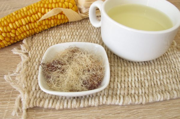 A dish filled with corn silk sits next to an ear of corn and a cup of soup.