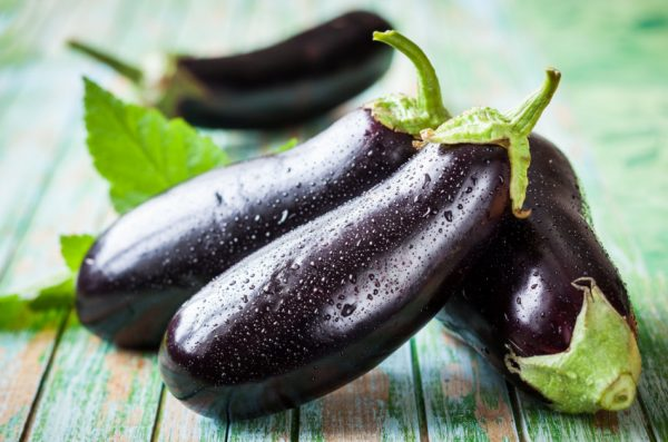 Four eggplants sitting on an old wooden table.