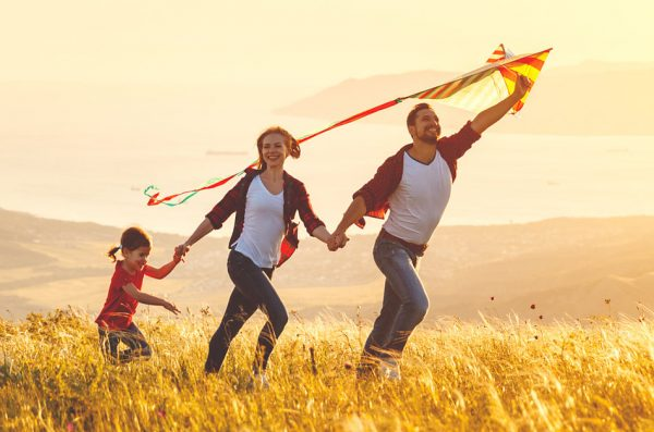 Happy family: father, mother, and daughter, run hand in hand with a kite.