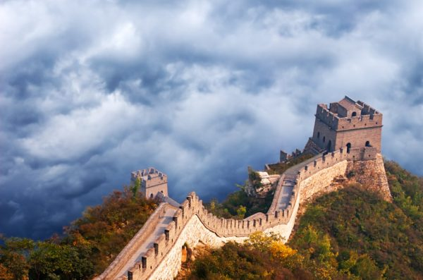 Great Wall of China seen from the air with storm clouds as a backdrop.