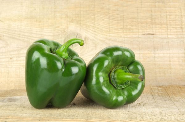 Two green bell peppers sitting on a wooden table.