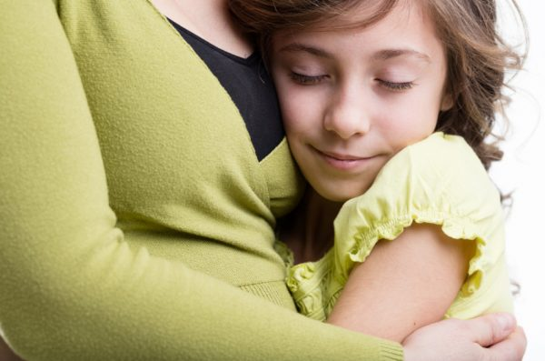 Daughter wrapped up in her mother's arms.