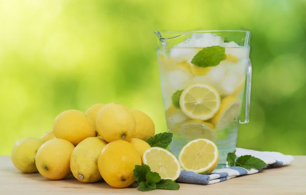 A pitcher of lemonade sits next to a stack of lemons on a wooden surface.