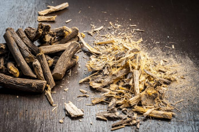 Licorice root and licorice root powder sitting on a wooden surface.