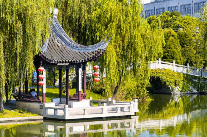A Chinese gazebo surrounded by weeping willow trees on a small lake within the Luzhi Ancient Town scenic area on a sunny day in Wuzhong China.
