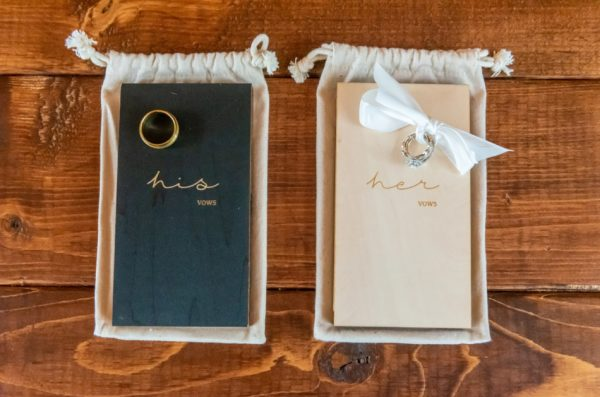"""A high angle shot of the bride and groom`s wedding rings on notebooks that say """"his vows"""" and """"her vows""""."""