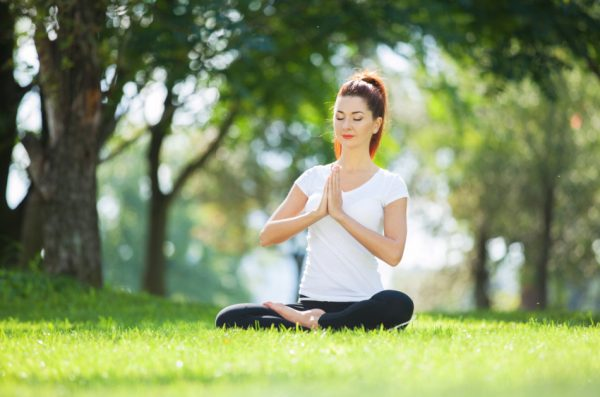 Young woman meditating in the park.