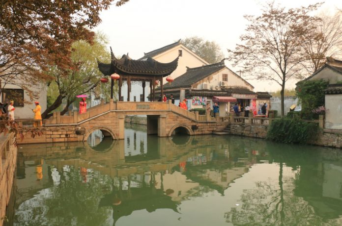 A bridge with Chinese-style pagoda over the waterway in Mudu, China.