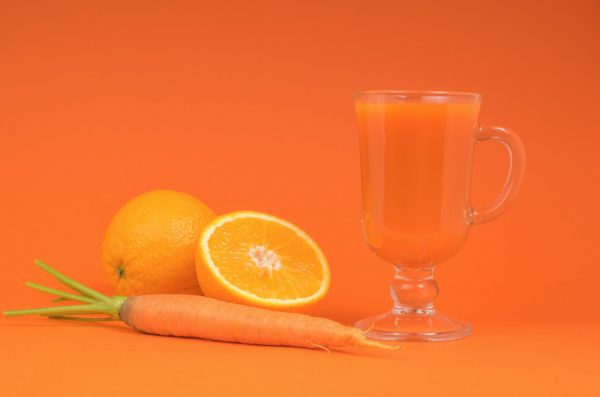 A carrot sits next to an orange and a glass mug full of an orange-carrot smoothie.