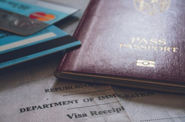 Photo of a passport and credit cards sitting on top of a travel document.