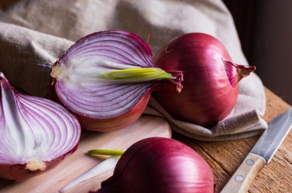 Purple onions sitting on a cutting board beside a knife.