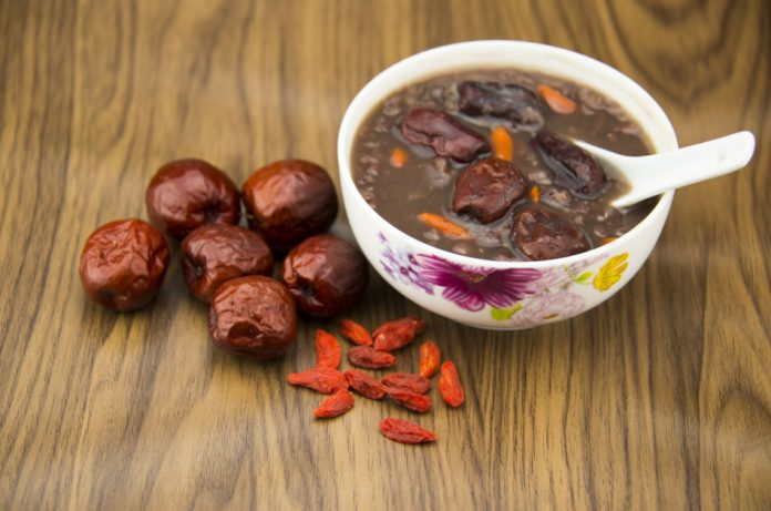 Red dates and wolfberry fruit sit on a table with a bowl of porridge.