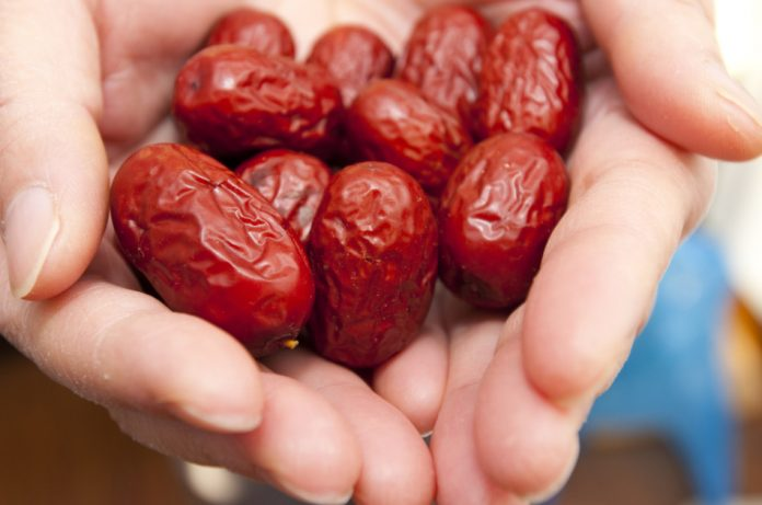 Closeup of a woman's outstretched hands filled with red dates.