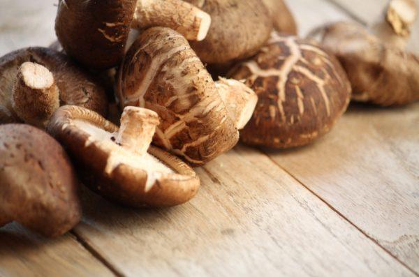 Shitake mushrooms sitting on a wooden surface.
