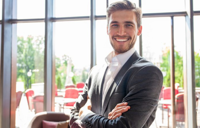 Smiling businessman with arms crossed standing in office.