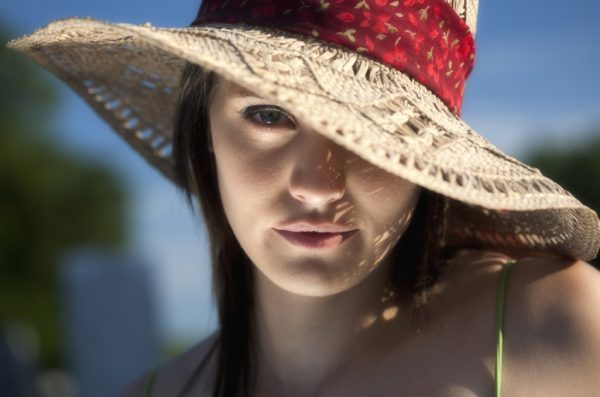 A close up portrait of a twenty something young woman in a sun hat with one eye showing.