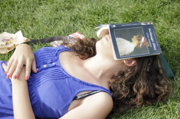 Young woman napping in the grass with a book over her face to block out the sun.