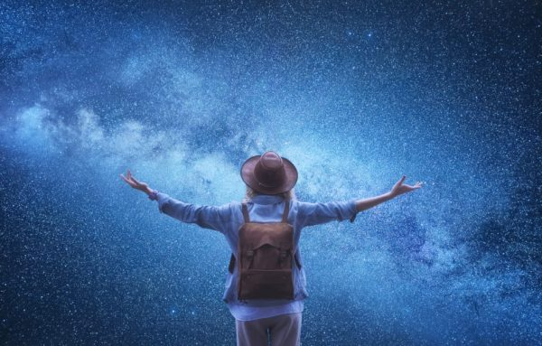 Female wearing hat and backpack with her back to the camera has arms outstretched in front of the night sky filled with stars.