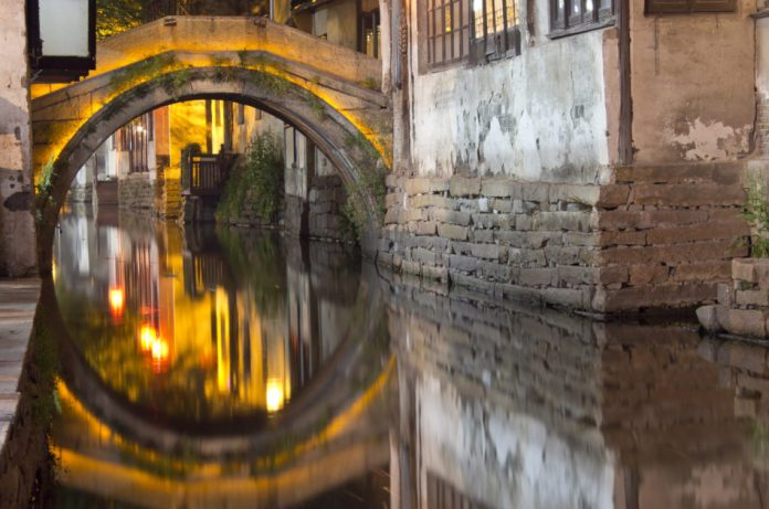 One of the many historical bridges in the water-town of Zhouzhuang, China lit up at night and reflecting in crystal clear water.
