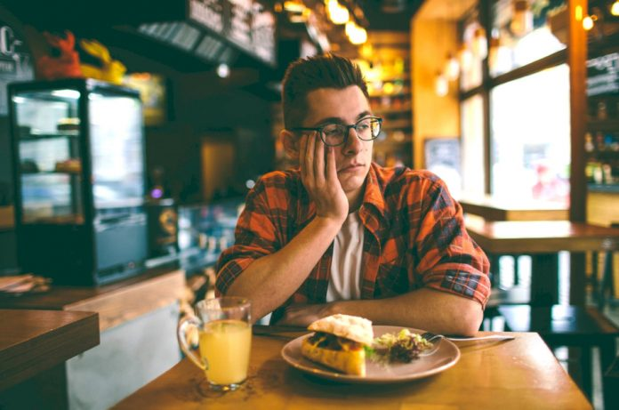 An unhappy man dines alone in a restaurant.