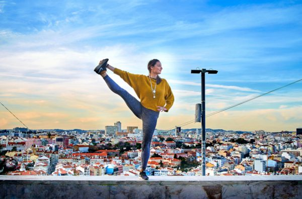 Young woman doing yoga exercise outdoors on the Lisbon city view background.