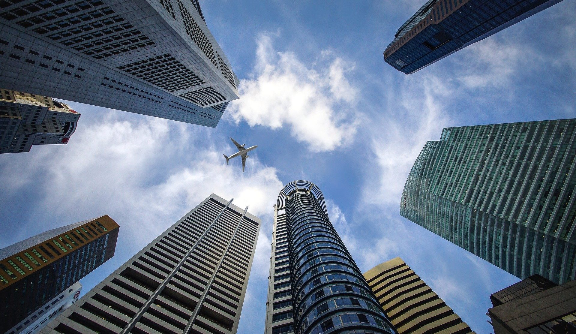 Looking straight up, a plane is seen flying above skyscrapers.