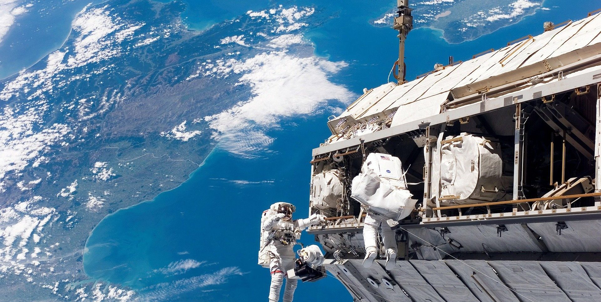 Two astronauts conduct a spacewalk.